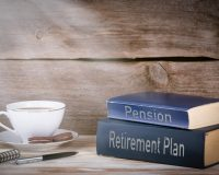 Retirement Plan and Pension. Stack of books on wooden desk